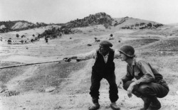 Seconda guerra mondiale, Troina, Sicilia. Un anziano indica a un ufficiale americano quale strada hanno percorso i tedeschi. Agosto 1943. © Robert Capa / International Center of Photography / Magnum Photos